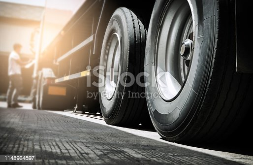 Close up truck tire and truck driver is checking safety around of semi truck.