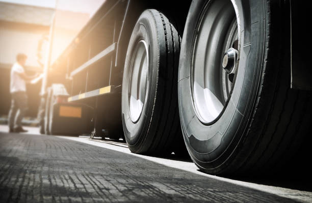 Truck inspecting and safety Close up truck tire and truck driver is checking safety around of semi truck. wheel stock pictures, royalty-free photos & images
