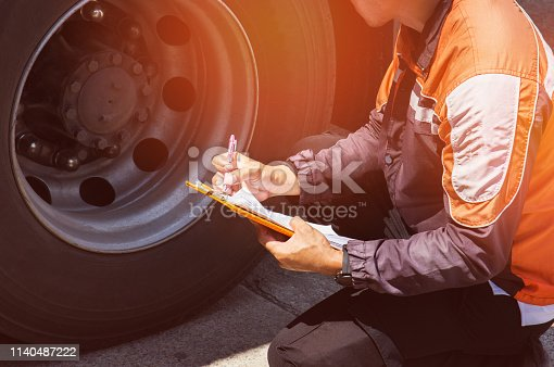 Truck driver is inspecting a truck tires