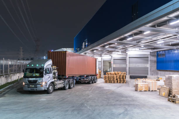 truck is carrying container is parking in front warehouse at night time - logistica foto e immagini stock
