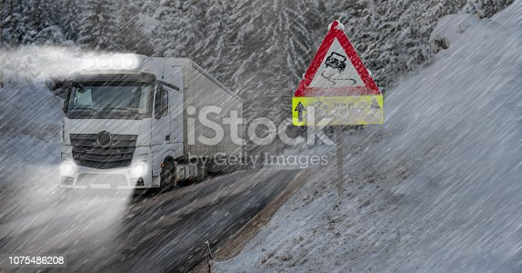 1127834626 istock photo Truck is driving on the road in winter 1075486208