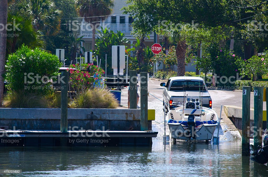 Truck is launching a small fishing boat at public ramp stock photo