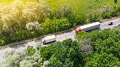 Truck logistic aerial. Wagon driving by the roadway between green forest.