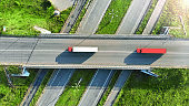 Truck logistics aerial. Two trucks motion by the highway intersection road between fields. View from drone.