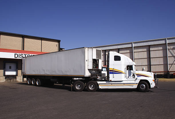 truck manouvering onto dock - lorries unloading stock photos and pictures