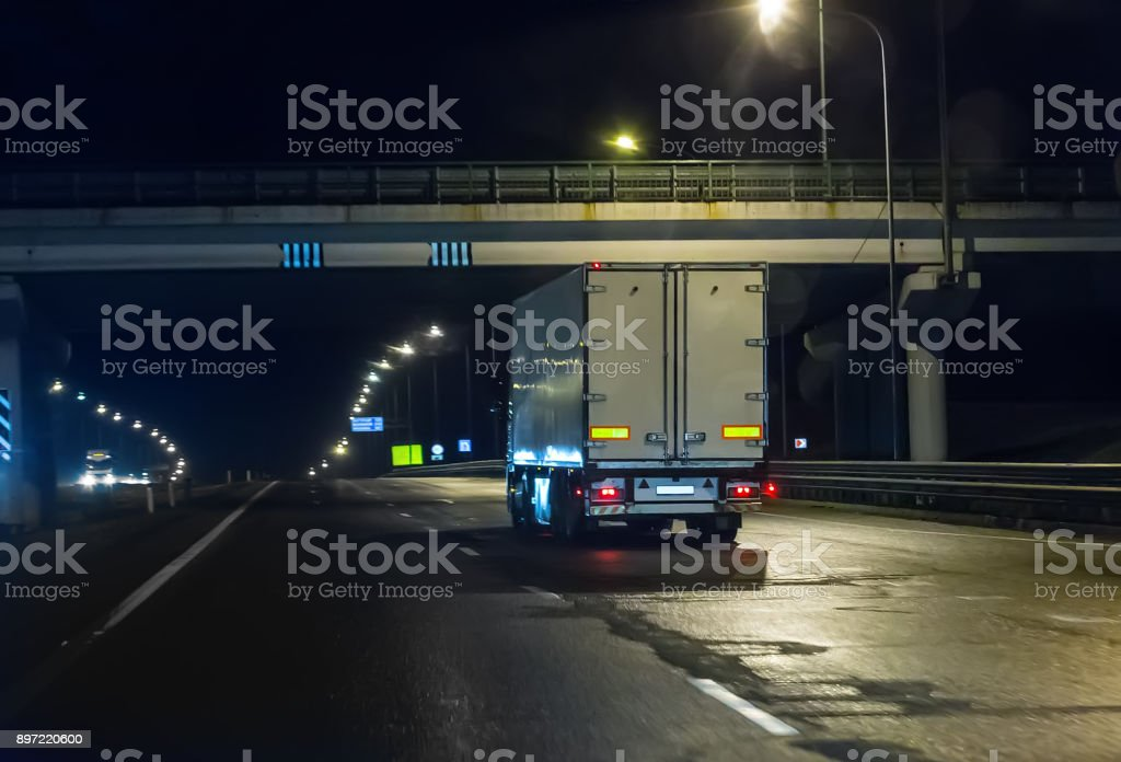 truck moves on highway at night stock photo