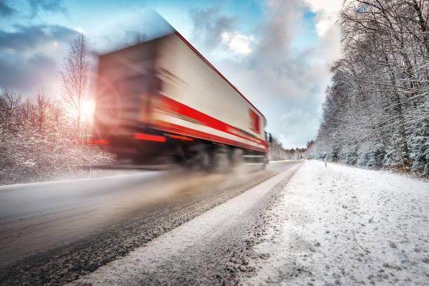 Truck on asphalt road in winter on sunny morning stock photo