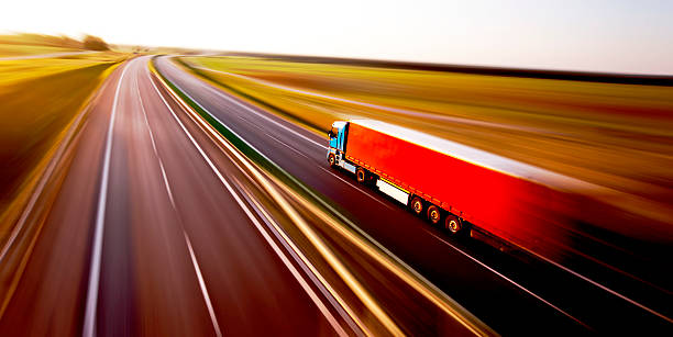 truck on asphalt road motion blur - international moving stock pictures, royalty-free photos & images