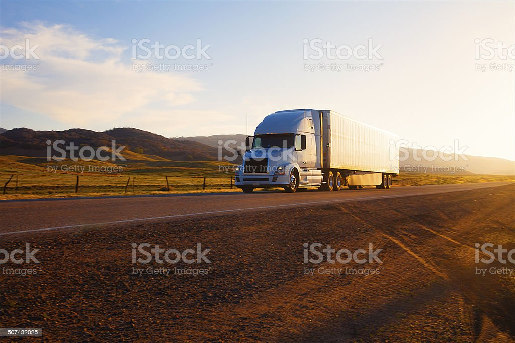 Truck on highway at sunset stock photo