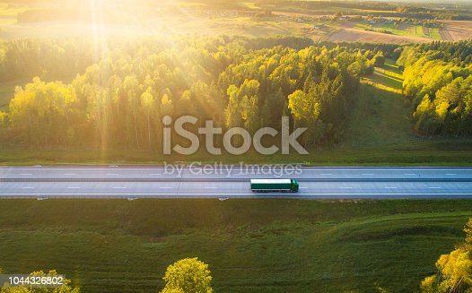 Truck on highway. Truck moving on road in evening. Cargo transportation background. Cargo shipping. Road with truck in sunlight and sun rays.