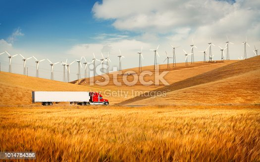 Truck going in the countryside with wind farm on the hills