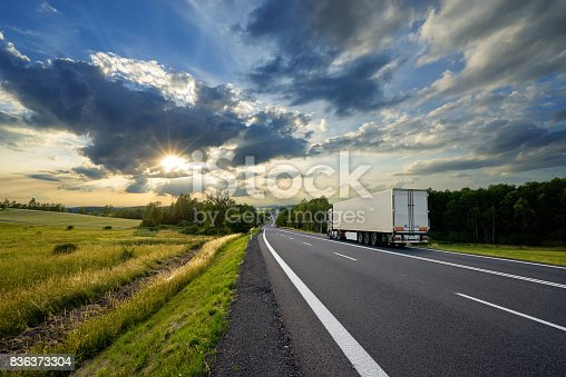 Truck transporting goods on asphalt road in rural landscape at sunset with dramatic clouds