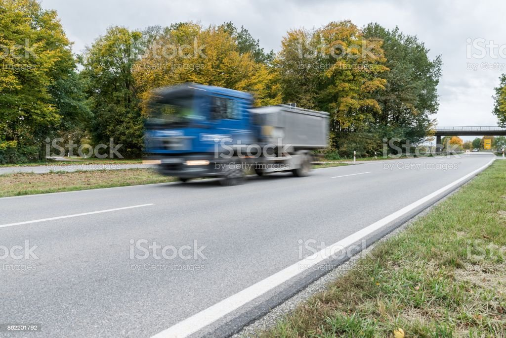 Truck passing by on a national highway, Germany stock photo