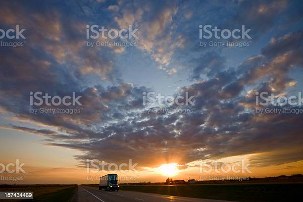Photo of Truck passing by on highway during a glorious sunset