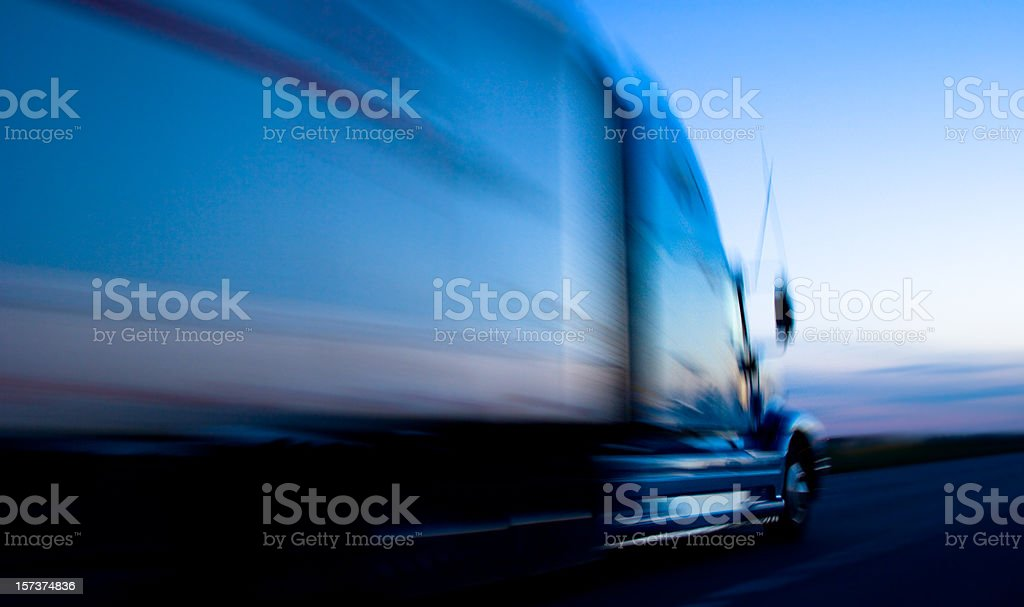Truck speeding down the freeway at dusk stock photo