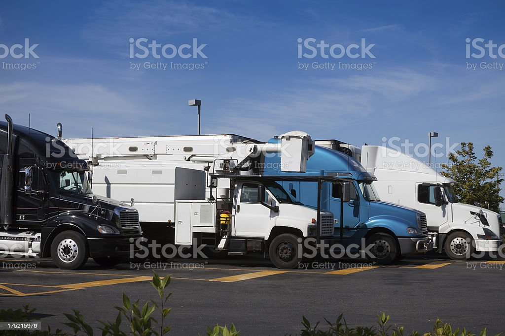 Various trucks parked at a truck stop parking lot.