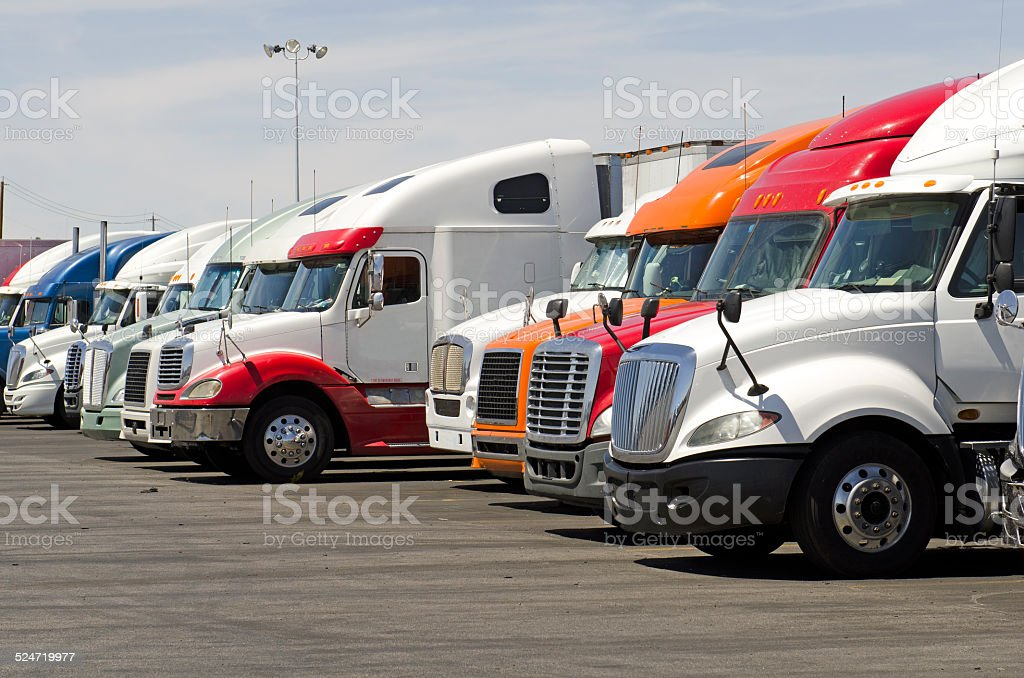 Over the road semi-truck tractors parked at a truck stop plaza