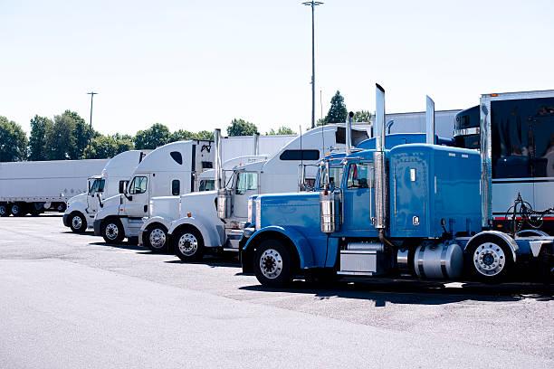 truck stop with row of big rigs semi trucks - aufgemotzte trucks stock-fotos und bilder