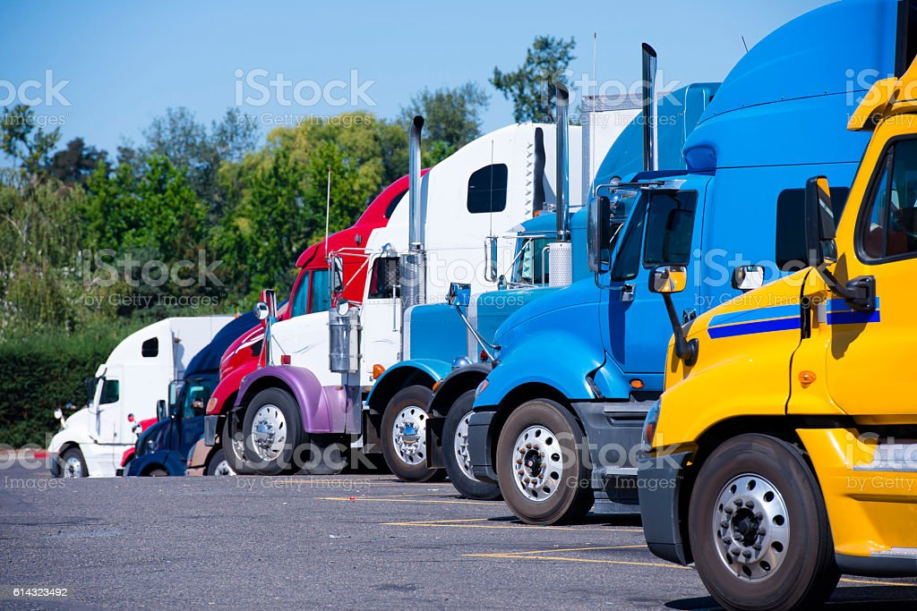 Truck stop with semi trucks various models standing in row stock photo