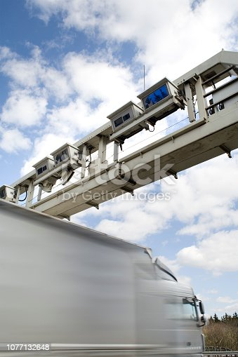 truck toll system at the highway - control bridge with passing truck, motion blur