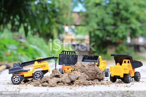 istock Truck toy car with sand and soil on the concrete floor with blur boken green environment  construction equipment at work ,construction concept, selective focus. 693525778
