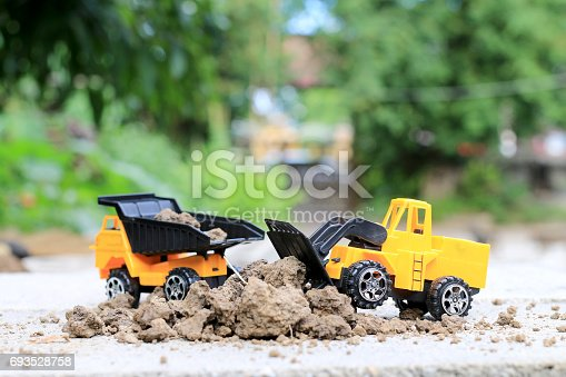 istock Truck toy car with sand and soil on the concrete floor with blur boken green environment  construction equipment at work ,construction concept, selective focus. 693528758