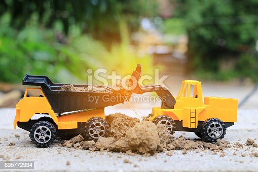 istock Truck toy car with sand and soil on the concrete floor with blur boken green environment  construction equipment at work ,construction concept, selective focus. 695772934