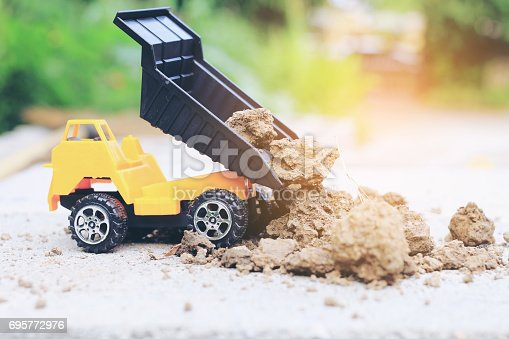 istock Truck toy car with sand and soil on the concrete floor with blur boken green environment  construction equipment at work ,construction concept, selective focus. 695772976