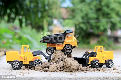 istock Truck toy car with sand and soil on the concrete floor with blur boken green environment  construction equipment at work ,construction concept, selective focus. 817282306