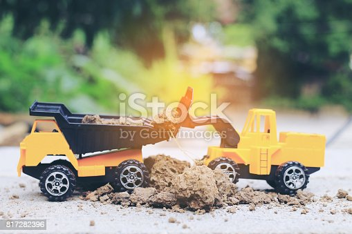 istock Truck toy car with sand and soil on the concrete floor with blur boken green environment  construction equipment at work ,construction concept, selective focus. 817282396