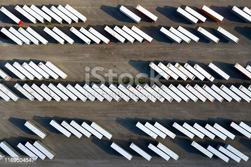 Rows of truck trailers and shiping containers in freight yard viewed from above.