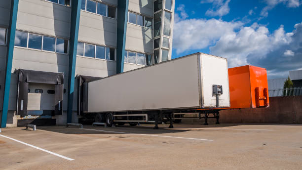 Truck Trailers at a dock Red and White Trailer at a Docking Bay of a distribution centre ready for Transport distribution center stock pictures, royalty-free photos & images