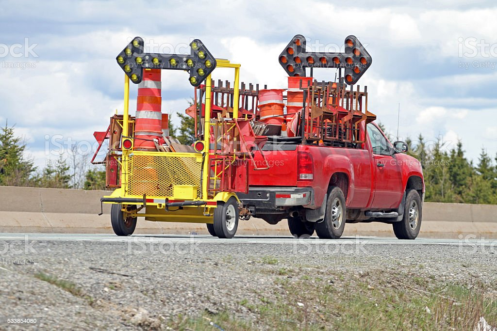 Truck Transporting Traffic Control Equipment On Highway To Construction Site stock photo