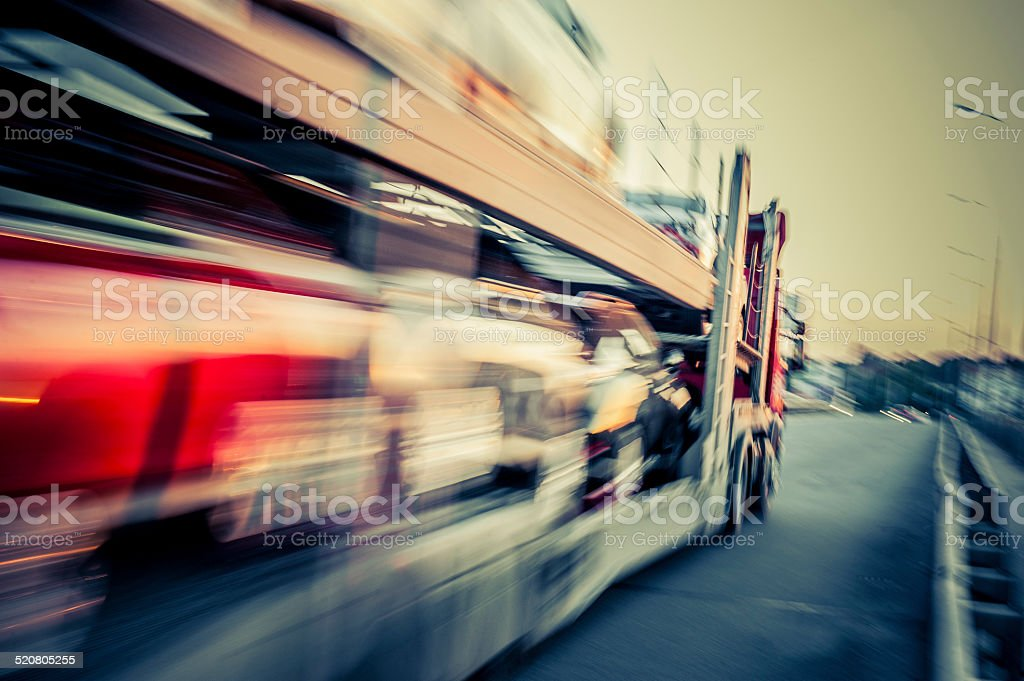 Truck transports cars, track in motion stock photo