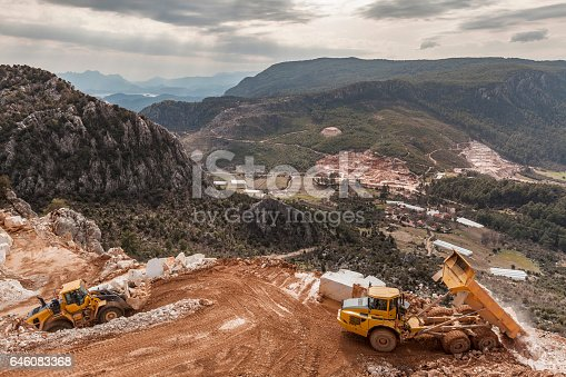 A truck is unloading rubble from a mountain side which is situated near a forest village.