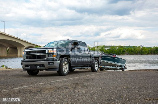 A truck backing up to a boat launch.