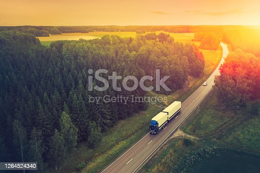 Aerial view of a truck travelling down a highway in a forest landscape in the Södermanland region of Sweden.
