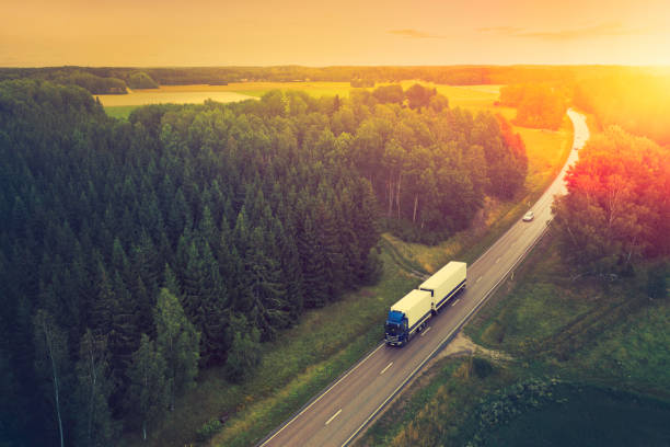 Truck with trailer at a highway through forests stock photo