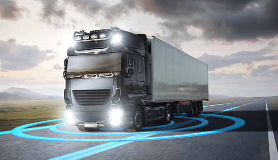 A moving truck on a highway. Blue graphics around the truck visualize an advanced driving technology.