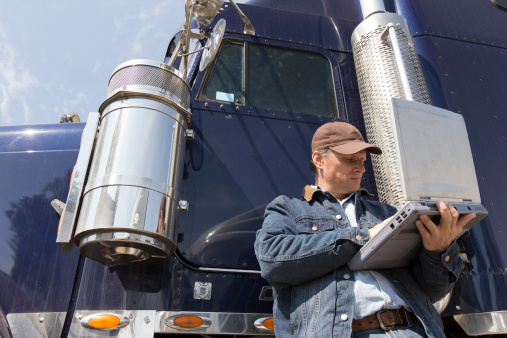 An image from the trucking industry of a truck driver on his computer.