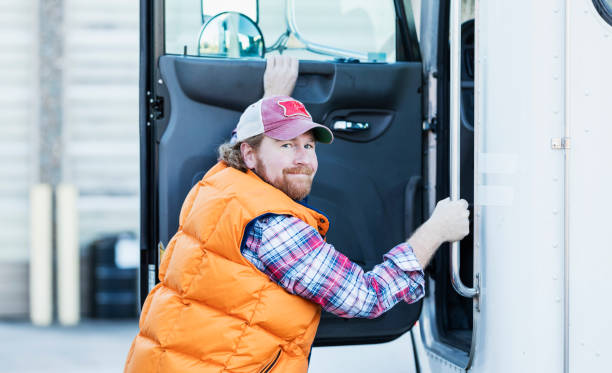 Trucker driver climbing into his semi-truck A truck driver standing outside his semi-truck at the open door, about to climb into the driver's seat. He is smiling and looking at the camera. He is a mature man in his 40s with red hair and beard. alongside stock pictures, royalty-free photos & images