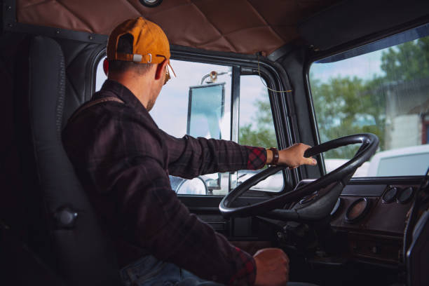Trucker in His 40s Inside Vintage Aged Semi Truck Tractor Cabin stock photo