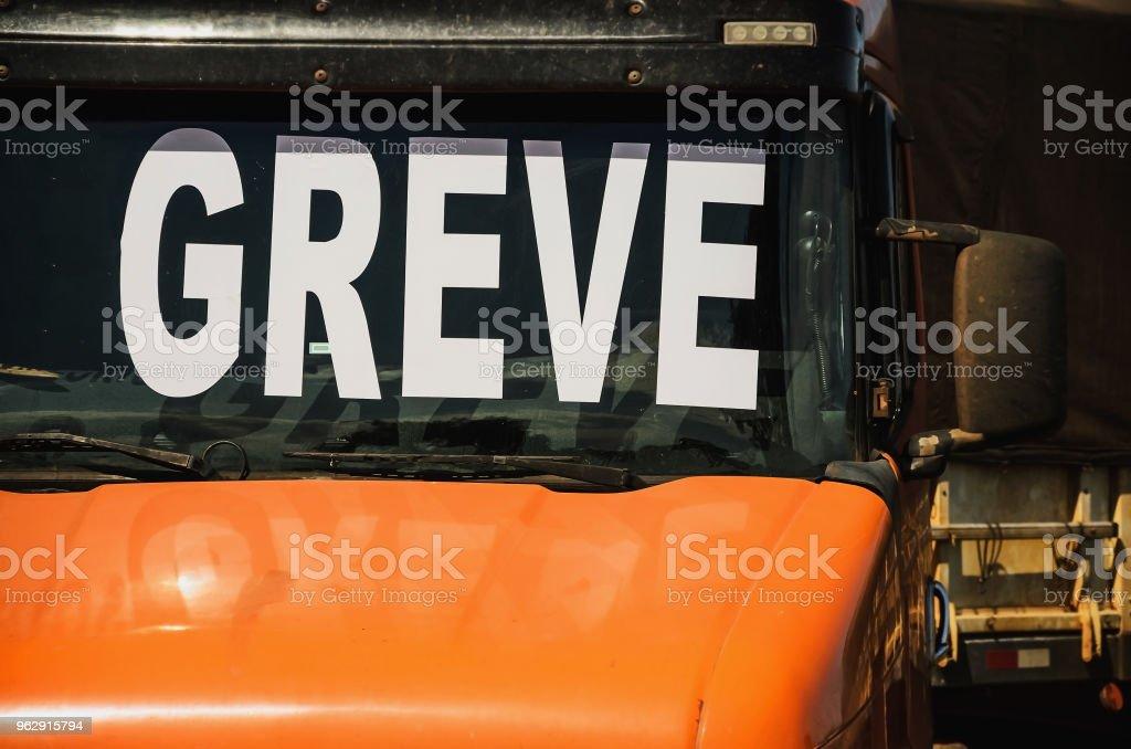 Caminhoneiro em greve. Caminhão de laranja com o para-brisa escrito Greve (em Português) - foto de acervo