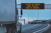 State of Emergency Obey Public Health Orders on an overhead highway sign during the Coronavirus pandemic, out of focus semi truck in foreground.