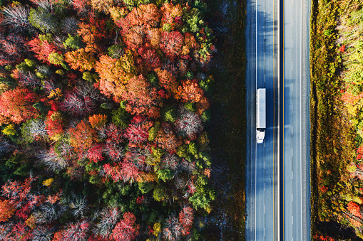 Aerial view of a semi truck driving on a highway on an October morning.