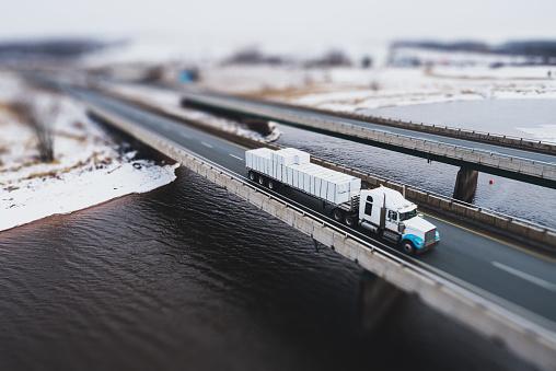 Aerial drone view of semi trucks crossing a tidal river.