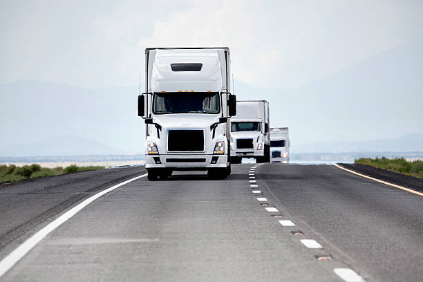 Trucking Industry Three white trucks in a convoy on an interstate highway caravan photos stock pictures, royalty-free photos & images