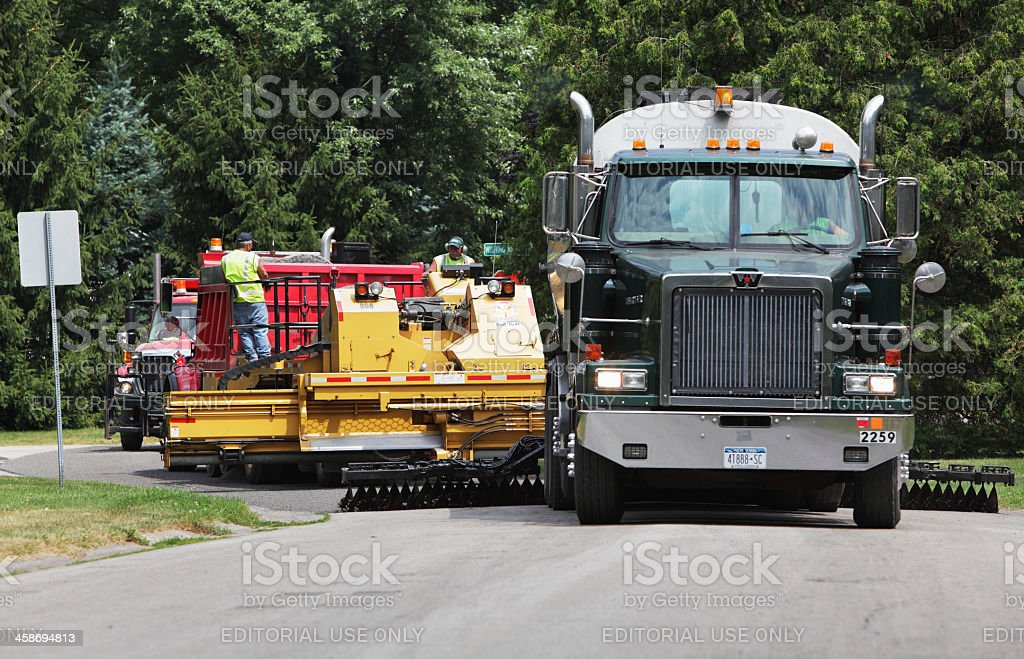 Workers using large trucks and specialized automated equipment are...