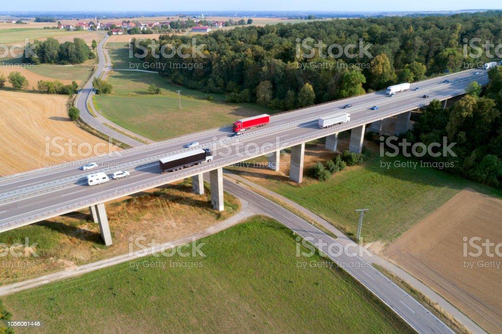 LKW und Autos gehen über Autobahnbrücke, Luftbild – Foto