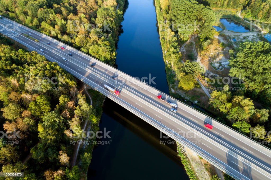 LKW und Pkw auf Autobahn Brücke über Fluss, Luftbild – Foto